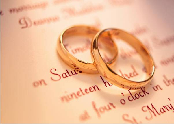 Two gold wedding bands sitting on wedding invitation